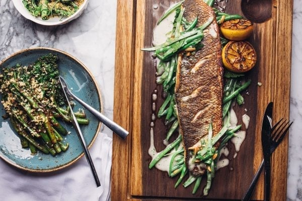 grilled european sea bass on wooden board and topped with peas