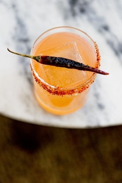 overhead view of cocktail with chilli on rim and grilled chilli pepper resting on rim of glass