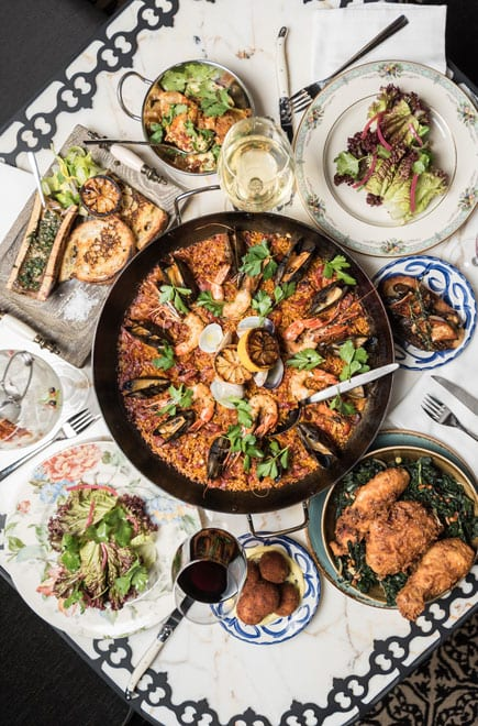 overhead photo of paella dish and side salads