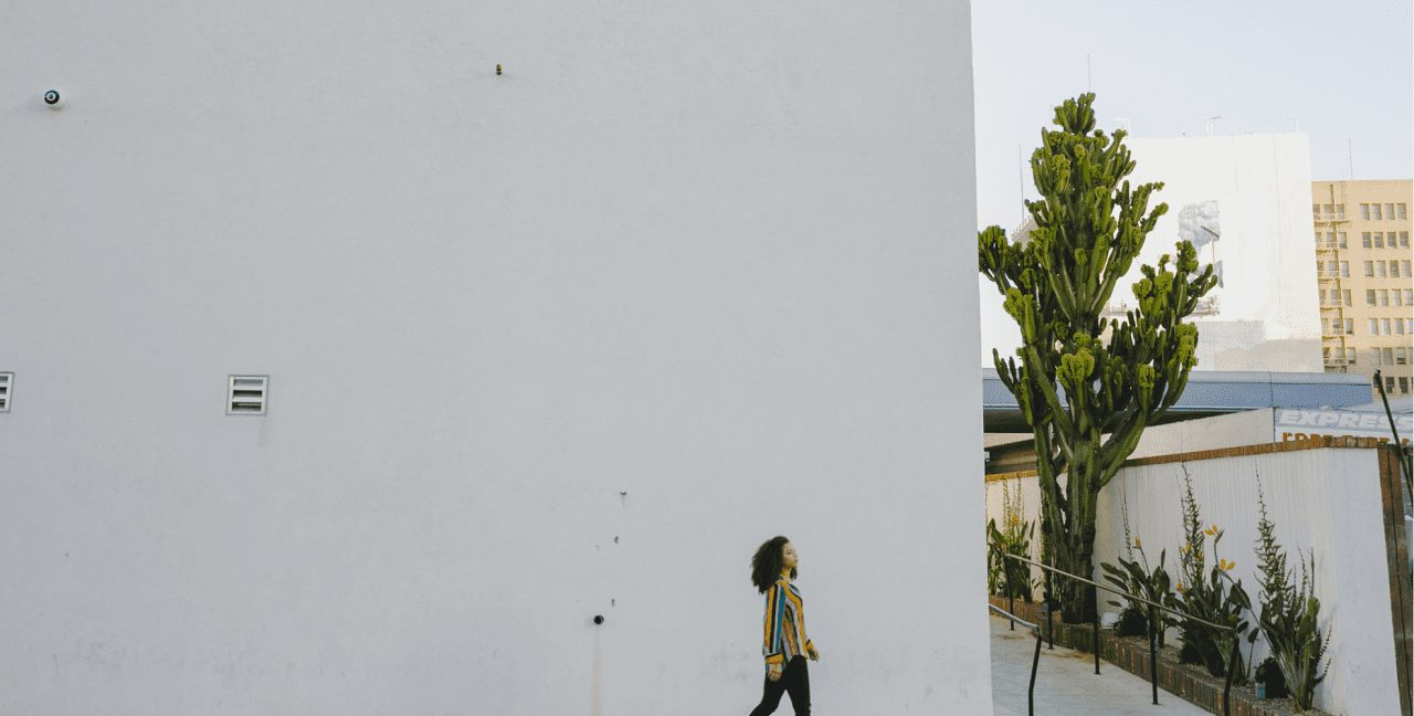 woman walking in front of large, empty building wall