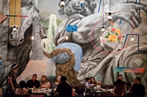 restaurant patrons sitting at tables in front of large mural