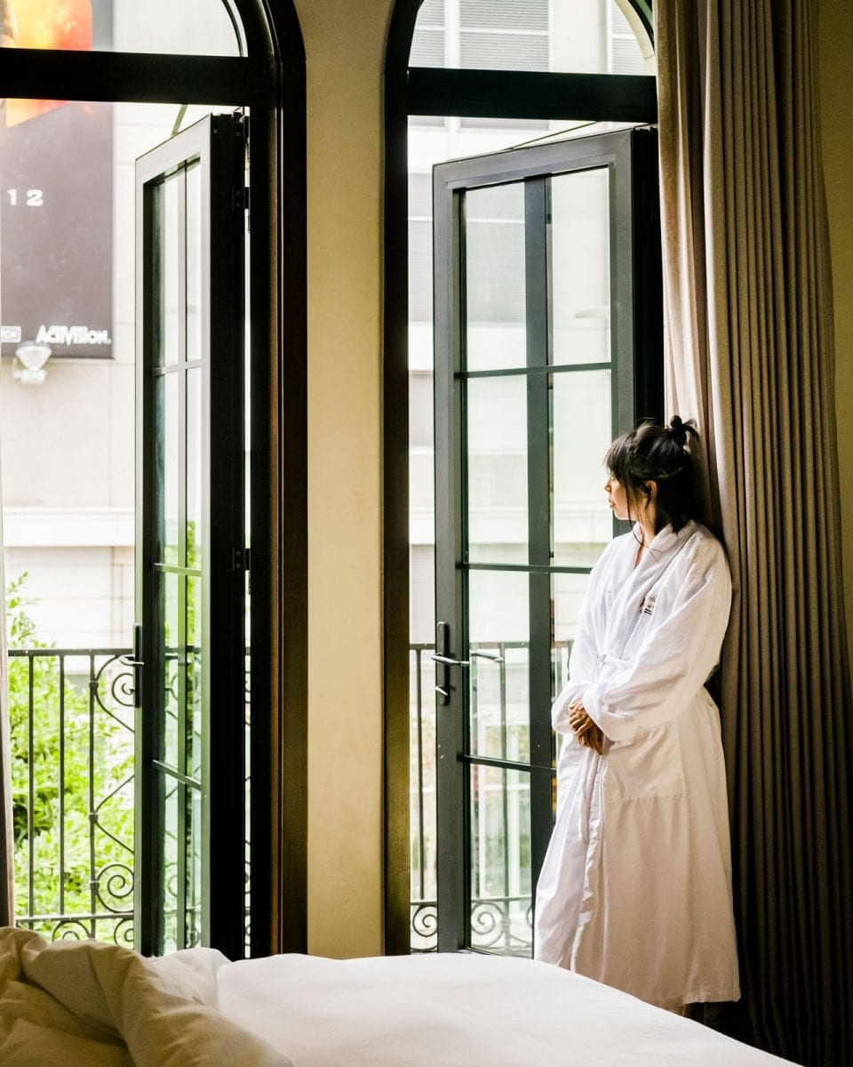 woman wearing bathrobe, looking outside hotel room from balcony door